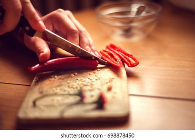Female hands cutting red chilly peppers