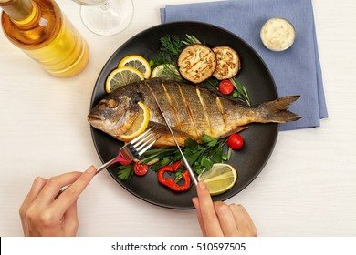 Female hands cutting tasty fish on plate