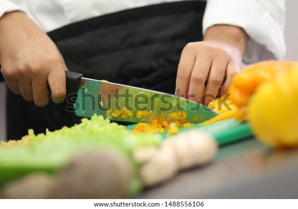 Female hands cutting yellow and green fresh vegetables with a silver knife over a cooking table.