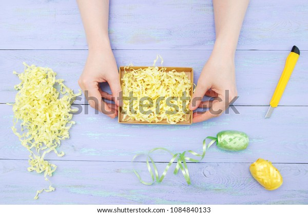 Female hands decorate a gift on a wooden violet background. View from above