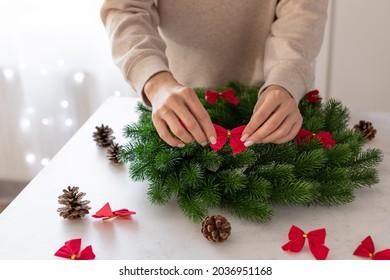female hands decorating Christmas wreath. Christmastime Decor. close-up. indoors