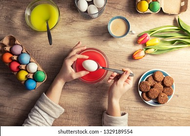 Female hands decorating Easter eggs, preparing Easter at home