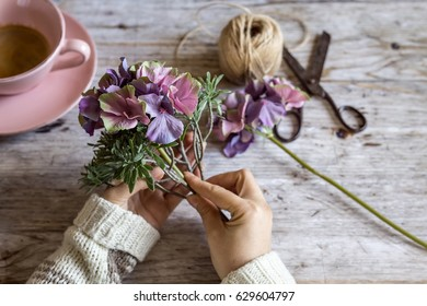 Female hands decorating with flowers with coffee