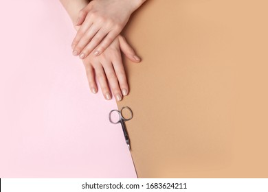 Female hands demonstrate freshly made manicure, in front of them are manicure scissors. Geometric two-color background.