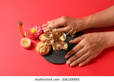 Female hands with diya lamp, burning candle, oil and cookies for celebration of Divaly on color background