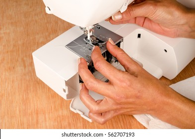 Female hands doing maintenance work on a domestic sewing machine