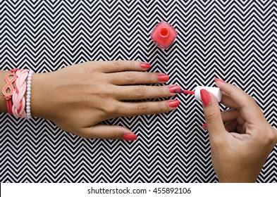 Female hands doing nail polish in coral color with summer bracelets