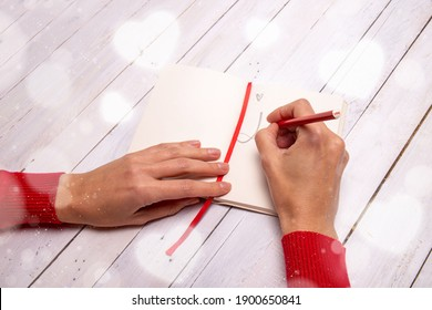 """Female hands drawing a sketch on a notebook. A """"love"""" sign on the pencil end and the bokeh effect all around enlives inspiration for a message to someone special."""