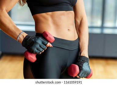 female hands with dumbbells with muscular athletic abs, female body
