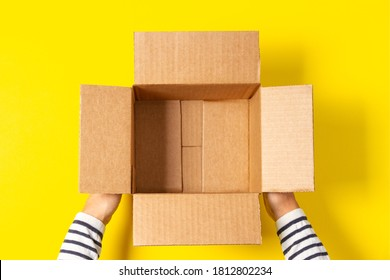 Female hands with empty open cardboard boxes on yellow background. Top view