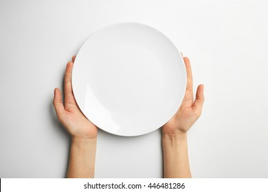 Female hands and empty plate isolated on white