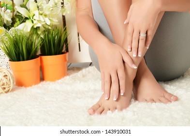 Weibliche Hände und Füße mit Maniküre und Pediküre