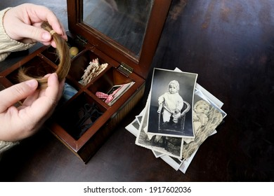 female hands fingering memorabilia in an old wooden box, a stack of retro photos, a lock of hair, vintage photographs of 1960, concept of family tree, genealogy, childhood memories