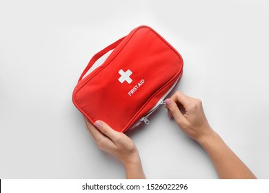 Female hands with first aid kit on white background