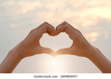 Female hands in the form of heart against sunlight in sunset sky, Love concept, Hands in shape of love heart, love Concept, Heart-shape hand gesture
