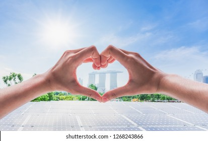 Female hands in the form of heart against sunlight behind landscape of solar panels energy field at singapore public park with blue sky,  New alternative energy from natural, Singapore