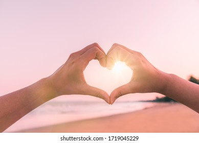 Female hands in the form of heart against sunlight in sunset sky on beach summer. Hands in shape of love heart, Love concept.