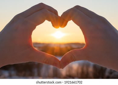 Female hands in the form of heart against the sky pass sunset beams. Hands in shape of love heart. Abstract background