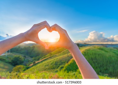 Female hands in the form of heart against sunlight behind landscape of  windmills plant in blue sky, Hands in shape of love heart - Love green energy.
