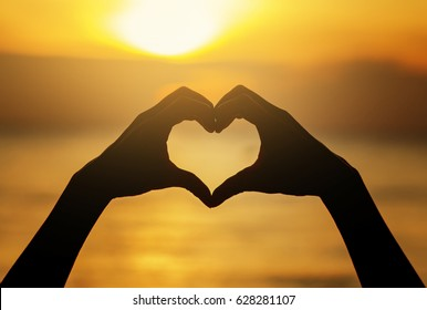 Female hands in the form of heart against the sky pass sun beams. Hands in shape of love heart