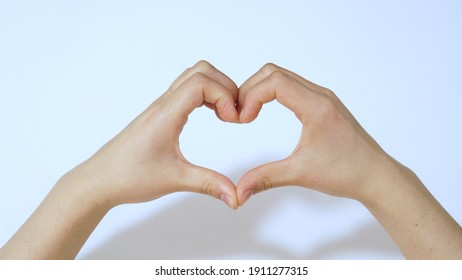 Female hands in the form of heart on white background under light.