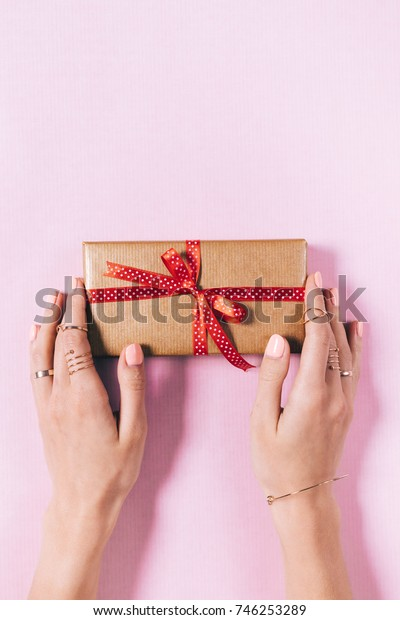 Female hands and a gift box with a red ribbon on a pink background top view