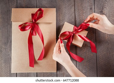 Female hands gift kraft packing with red ribbon. top view.