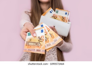 Female hands giving euro banknotes on pink background