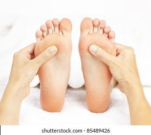 Female hands giving massage to soft bare feet
