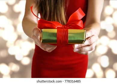 Female Hands giving a present with red ribbon for Valentines day / birthday /Christmas with golden lights background