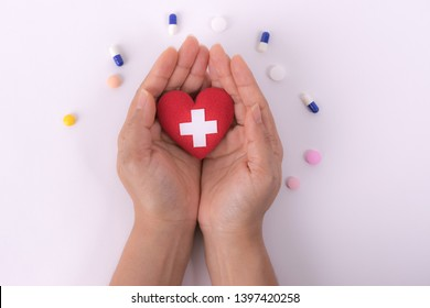 Female hands giving red heart with white cross aymbol on white paper background. International Nurses Day. Healthcare and medical concept.