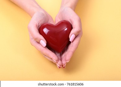 Female hands giving red heart, isolated on gold background