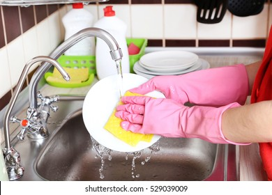 Female hands in gloves with sponge washing dish