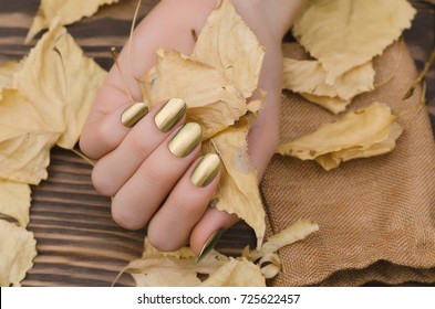 Female hands with gold chameleon nail design holding fallen leaves.