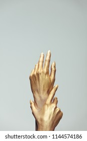 Female hands in gold paint on grey background. Hands of woman painted with golden color.