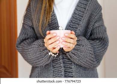 female hands in a gray knitted cardigan holding a pink cup with coffee