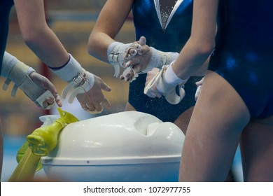Female hands gymnasts clapping white chalk powder at the championship