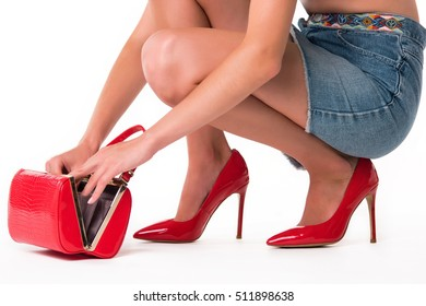 Female hands with handbag. Woman in red high heels. Where is my wallet. Open and look what's inside.