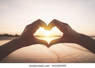 Female hands heart shape on nature bokeh sun light flare wave and blur tropical sunset beach abstract background. Copy space of happy love travel and freedom in nature concept. Vintage tone color.