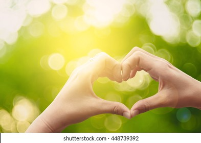 Female hands heart shape on nature green bokeh sun light flare and blur leaf abstract background. Happy love and freedom concept. Vintage tone color style.