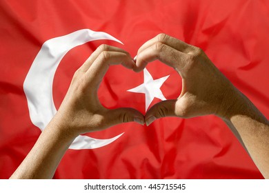 Female hands heart symbol with Turkey flag in background