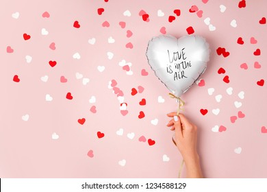 Female hands hold Balloon of heart shaped foil on pastel pink background. Love concept. Holiday celebration. Valentine's Day or wedding/bachelorette party decoration. Metallic balloon