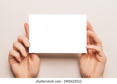 Female hands hold a blank sheet of paper on a beige background. Advertising space