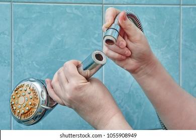 Female hands hold a broken shower head in the bathroom with blue tiles.