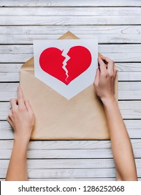 Female hands hold a brown envelope with a sheet of paper which shows a broken red heart. Old grey wooden background. The concept of breaking relationships, betrayal and nostalgia.
