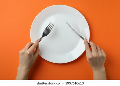 Female hands hold cutlery over the empty plate on orange background
