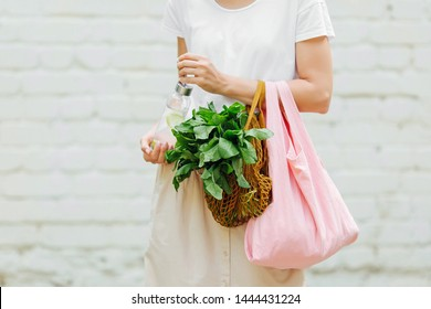 Female hands hold eco bag of vegetables, greens and reusable water bottle. Zero waste. Sustainable lifestyle concept.