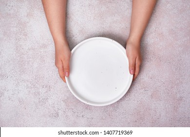 female hands hold an empty ceramic plate (tray). view from above. copy space