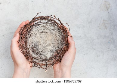 Female hands hold an empty nest with Easter colorful eggs. Top horizontal view abstract composition. Caring and saving up concept