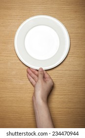 A female hands hold a empty(blank) white dish(plate) on the wood table(desk), top view at the studio.